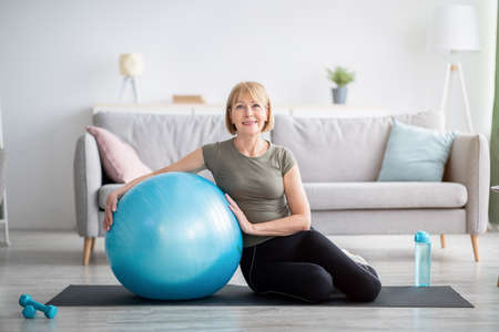 Full length portrait of happy mature woman resting on yoga mat with fitness ball, smiling at camera indoors, free space. Cheerful senior lady taking break from her domestic training Foto de archivo