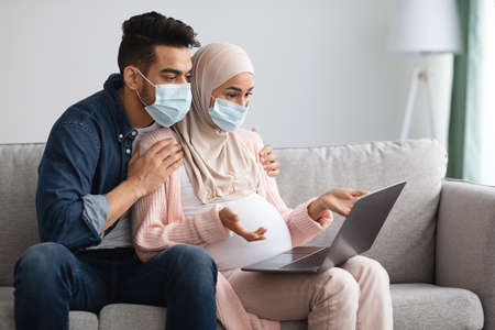 Concerned Pregnant Muslim Couple In Medical Masks Using Laptop At Home, Frustrated Islamic Spouses Reading Coronavirus Statistic News While Sitting Together On Couch In Living Room, Free Space