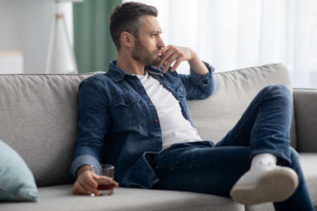 Depression, crisis concept. Sad middle-aged bearded man sitting on sofa, drinking alcohol at home, feeling lonely and sick, holding glass of whiskey and looking through the window, copy space