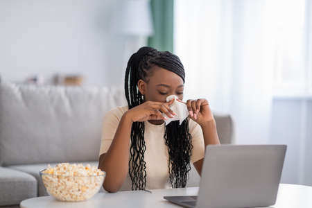 Sad african american woman weeping and sneezing nose while watching soap opera, eating popcorn at home. Upset young black lady watching melodrama on laptop and crying, living room interior, copy space