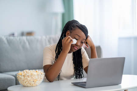 Upset young black lady watching melodrama on laptop and crying, living room interior, copy space. Sad african american woman weeping while watching soap opera, eating popcorn at home