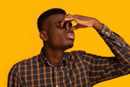 Bad Smell. Young african american guy closing his nose with fingers, irritated black millennial man feeling disgusted by terrible odor, standing isolated over yellow background, closeup shot