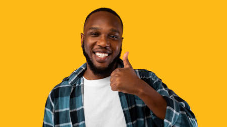 I Like It. Cheerful African American Man Gesturing Thumbs Up Approving Something Posing Standing Over Yellow Studio Background, Smiling To Camera. Advertisement Banner. Panorama