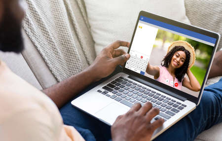 Young black man communicating to his girlfriend on video chat, using laptop computer for distance conversation at home. Millennial guy having videoconference with his wife, indoors Stock fotó