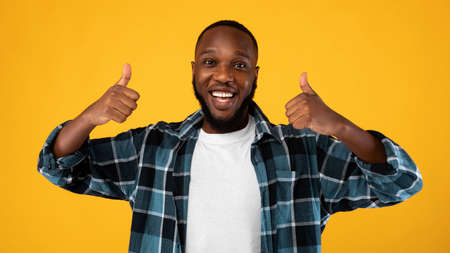 Positive Black Man Gesturing Thumbs Up To Camera With Both Hands Approving Something Standing Posing On Yellow Background In Studio. I Like It Concept. Advertisement Banner. Panorama
