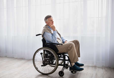 Full length portrait of handicapped senior man in wheelchair feeling desperate and lonely, looking out window indoors. Concept of disability and old age, depression in senior adults