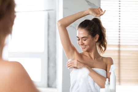 Woman Applying Antiperspirant On Armpits Preventing Sweating Standing In Bathroom