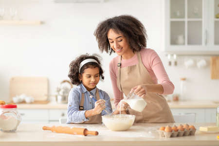 Happy black woman and daughter making pastry in kitchen