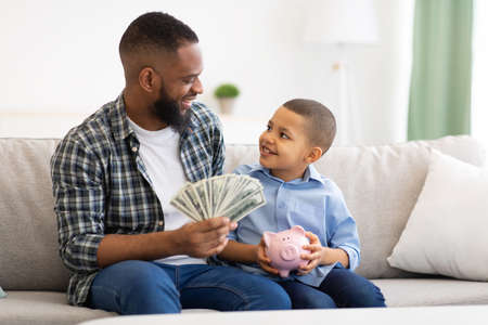 Father Teaching Son Budget Planning Putting Money In Piggybank Indoors