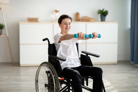 Physical rehabilitation for disabled people. Handicapped teenager in wheelchair making exerises with dumbbells at home Imagens