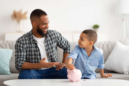Father And Son Putting Personal Savings Money In Piggybank Indoor