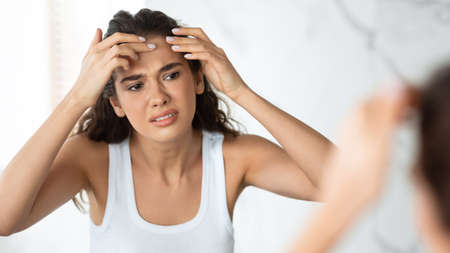 Sad Woman With Acne Issue Squeezing Pimple On Forehead Indoor
