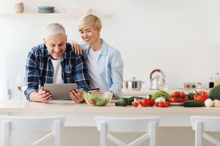 Happy senior couple use tablet, credit card, ordering food delivery in grocery in market doing shopping