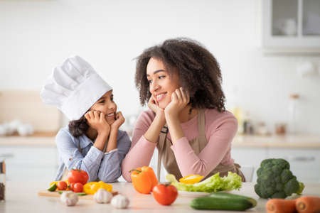 African american mother and daughter cooking tasty salad Imagens