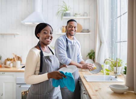 Cheerful African American couple washing dishes together indoors, free space. Keeping house tidy Imagens