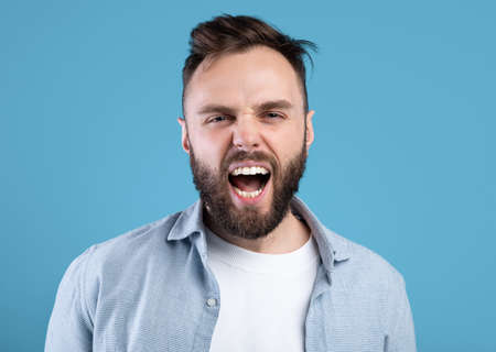 Enraged bearded guy shouting in anger, expressing his aggression over blue studio background Foto de archivo