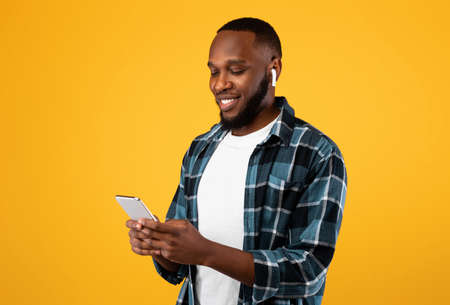 African Man Using Phone Wearing Earbuds Standing Over Yellow Background Stockfoto