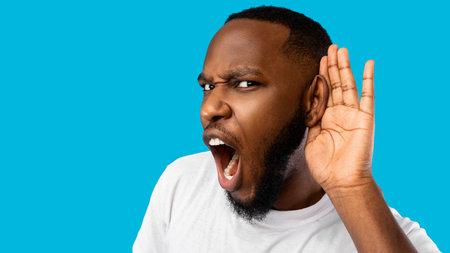 Funny Black Guy Listening Holding Hand Near Ear, Blue Background