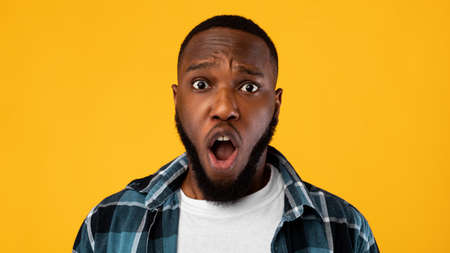 Shocked African Guy Looking At Camera Posing On Yellow Background
