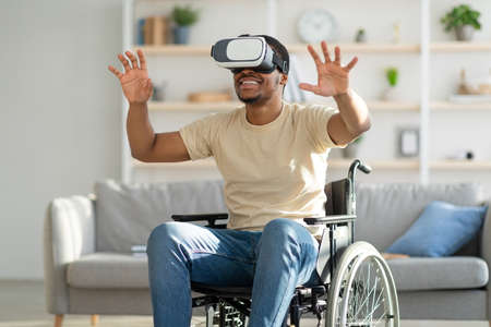 Handicapped black man in wheelchair exploring augmented reality in VR headset at home. Futuristic technologies concept
