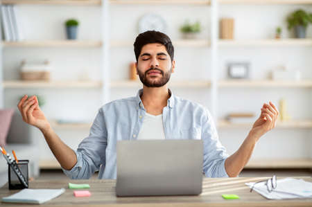 Keep calm. Arab freelancer meditating while working on laptop, sitting with eyes closed at his workplace at home interior