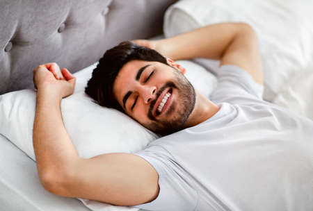 Happy wellslept arab man awakening and stretching hands lying in modern comfy bed at home 版權商用圖片