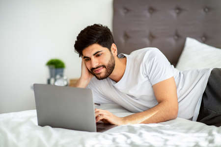 Cheerful arab man browsing internet on laptop while lying on bed at home, using computer in morning