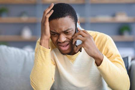 Closeup of sad black guy having conversation on phone Foto de archivo