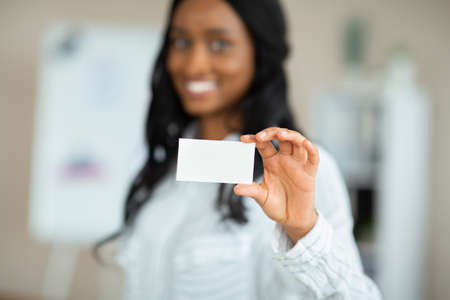 Black female entrepreneur holding empty business card at company office, mockup for design Stockfoto
