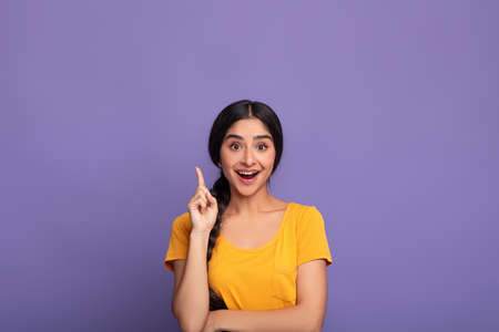 Excited indian woman has great idea and points up
