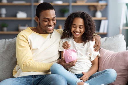 Black girl and father putting coin into piggy bank