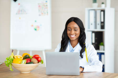 Cheerful black female dietitian using laptop pc, creating online weight loss program at modern clinic, free space