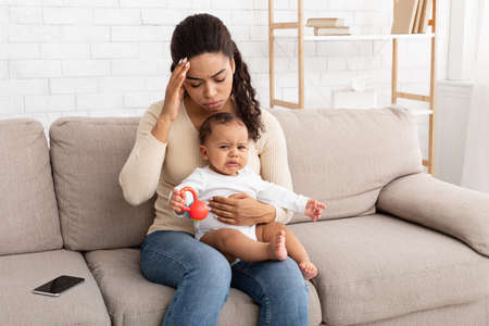 Black Mom Having Headache Sitting With Crying Baby At Home