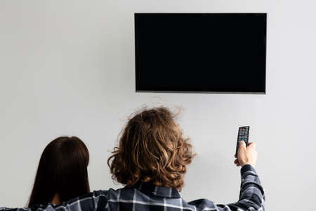 Couple Pointing Remote Control On Empty TV Screen Indoor, Back-View