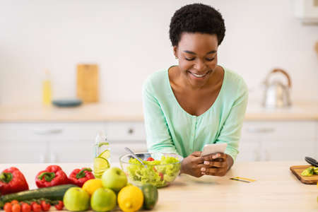 Happy African Lady Using Smartphone With Cooking Application In Kitchen