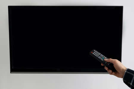 Hand Pointing Remote Control At Empty TV Screen At Home