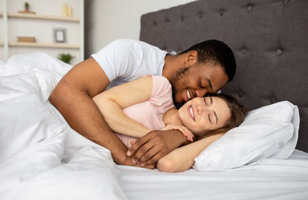 Multiracial couple cuddling in bed at home, hugging each other, having intimate after waking up in morning