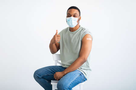 Vaccinated Male Patient Wearing Face Mask Gesturing Thumbs-Up, White Background