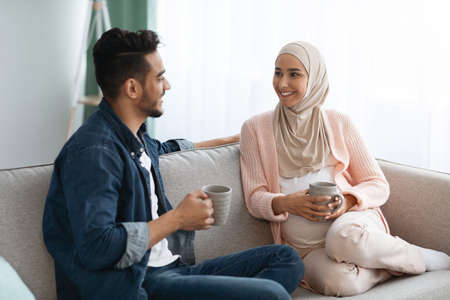 Cheerful Pregnant Muslim Couple Resting Together At Home, Drinking Coffee And Chatting Фото со стока