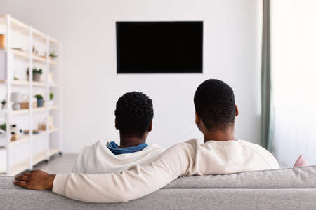 Black family watching TV with mockup, sitting on the couch Stock Photo