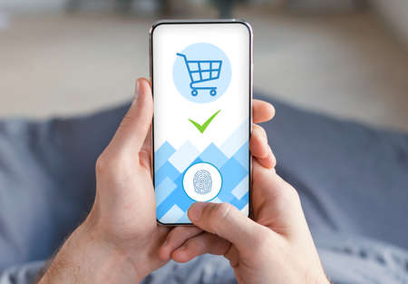 Guy Using Phone Lying In Bed, paying with touch