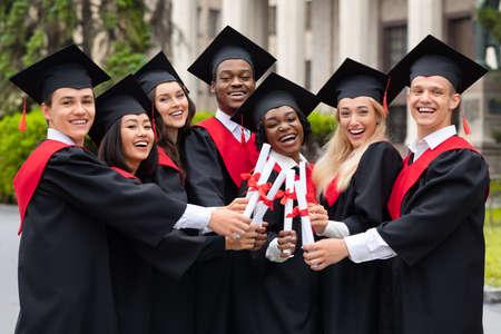 Diverse International Students With Diplomas Celebrating Graduation