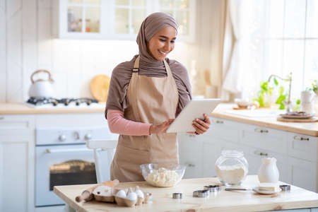 Happy Muslim Housewife In Hijab Using Digital Tablet In Kitchen While Baking Reklamní fotografie