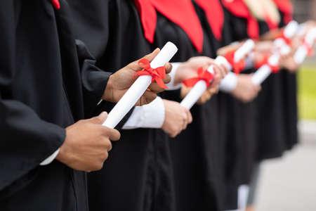 Cropped of international group of graduates holding diplomas