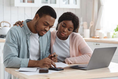 Portraif Of Young African Couple Sitting At Table In Kitchen, Reading Documents Standard-Bild