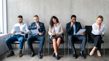 Multiethnic Applicants Waiting For Job Interview Sitting In Row Indoors Stock Photo
