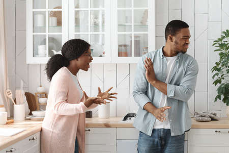 PMS Concept. Furious Young African American Woman Screaming At Husband In Kitchen
