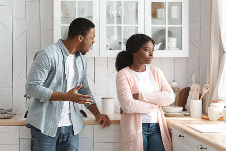 Young Black Couple Quarreling At Home, Indifferent Woman Ignoring Her Screaming Husband