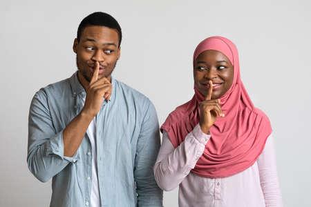 Muslim black couple make silence sign, keep forefingers on lips