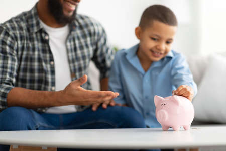 Father And Son Putting Personal Savings In Piggybank Indoors, Cropped